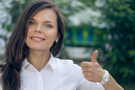 winning mood: Portrait of a young successful woman in a white shirt with thumb up on a green background outdoors. Smiling pretty girl.