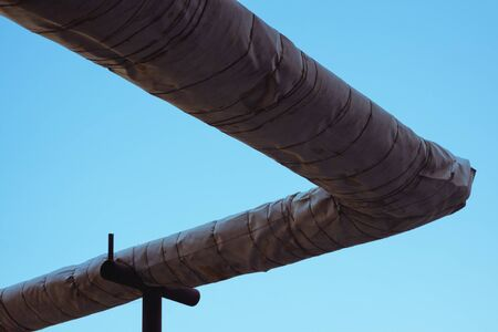 insulated: Insulated heating pipes outdoors against the sky. Stock Photo