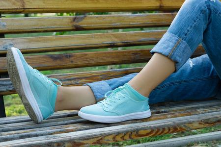 Vrouwelijke voeten in jeans en sportschoenen op een bankje close-up. Meisje rusten op een bank na een wandeling in het park.