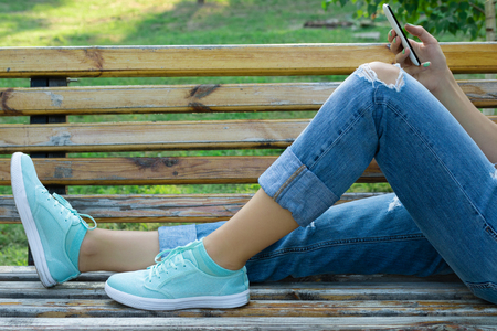 Female feet in blue jeans and a mobile phone in hand close-up. A girl resting in a park on a bench and using a mobile phone.
