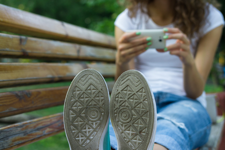 sitt: Soles shoe closeup. In the background girl in jeans using a mobile phone sitting on a bench. Rest in the park. Stock Photo