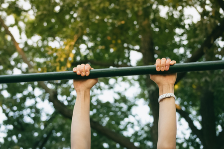 outdoor exercise: Female hands on the horizontal bar outdoors in the park. Sports activities on fresh air in the summer. Stock Photo