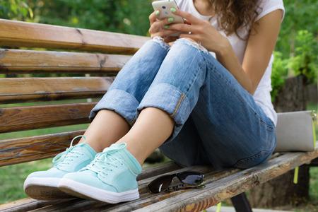 Muchacha en pantalones vaqueros se sienta en un banco del parque y el uso de un teléfono móvil