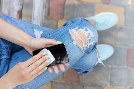 Female hands wipe the touch screen phone antibacterial wipes. Remove dust and dirt from the phone while walking. Stock Photo