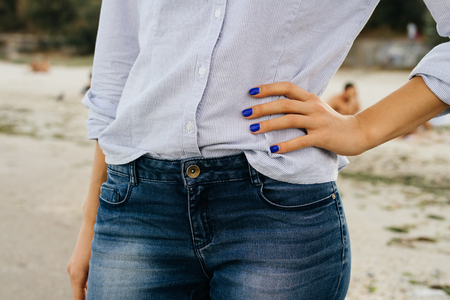 Details of womens clothing. The woman in jeans and shirt standing on the beach. Close-up, outdoors.
