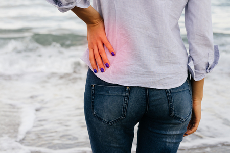 in the back: Low Back Pain. The woman in jeans and shirt standing on the shore and holding her lower back.