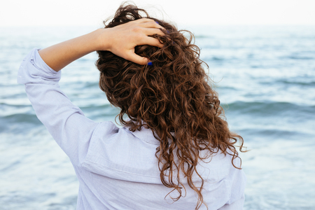 cabello rizado: Mujer joven en camisa mirando el mar y mantiene su cabello. Volver vista de primer plano.