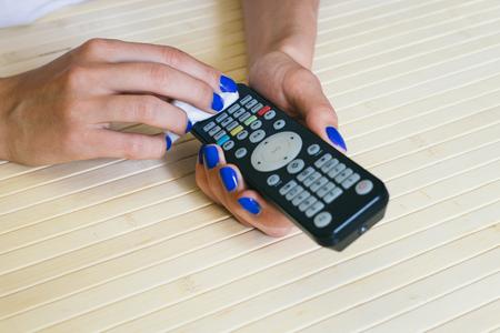 Female hands with blue manicure wipe dust remote control Standard-Bild