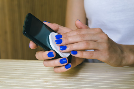 Female hands with blue manicure wipe dust touch screen mobile phone