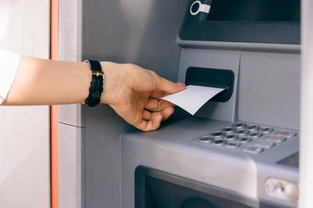 efectivo: Mano femenina que sostiene un recibo obtenido de la ATM después de retirar dinero en efectivo. El terminal bancaria externa.