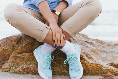 his shirt sleeves: Woman in beige pants and a denim shirt and turquoise sneakers sitting on a rock by the sea. Shirt sleeves rolled up, watch on his arm, a blue manicure. Arms and legs crossed. Close-up, outdoors.