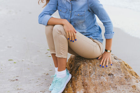 rolled up sleeves: Woman in beige pants and a denim shirt and turquoise sneakers sitting on a rock by the sea. Shirt sleeves rolled up, watch on her arm, a blue manicure. Stock Photo