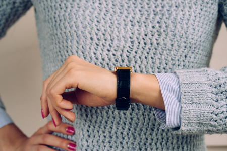 luxury watches: Woman in a gray sweater checks the time on a wrist watch close-up.
