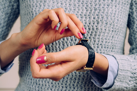 fastens: Womens hands with bright manicure fastens the strap on the watch. Stock Photo