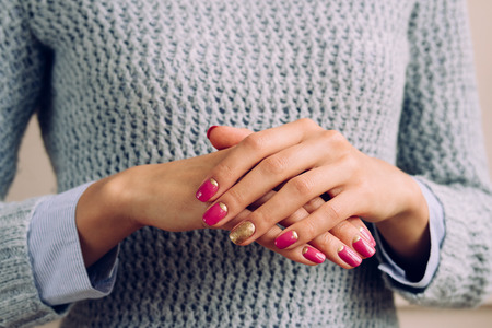 hand care: Woman in a gray knitted sweater shows pink and golden manicure closeup.