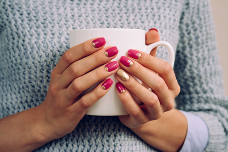 Woman in the gray sweater holding in her hands with a bright nail Polish large white Cup closeup. Archivio Fotografico
