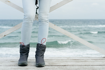 casual fashion: Female feet in jeans and sports boots on wooden boards against the sea close-up. Stock Photo