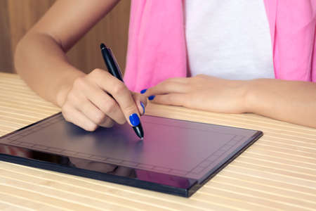 manicure pink: Woman in pink scarf and blue manicure draws on the tablet at a wooden table close-up. Stock Photo