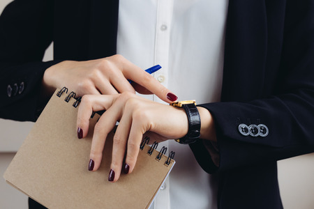 Woman in a business suit and dark red manicure holding a notebook and looks at his watch close-up