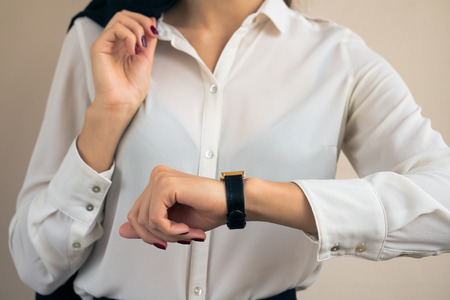 Woman in business attire looking the time on hand watch closeup Stock Photo