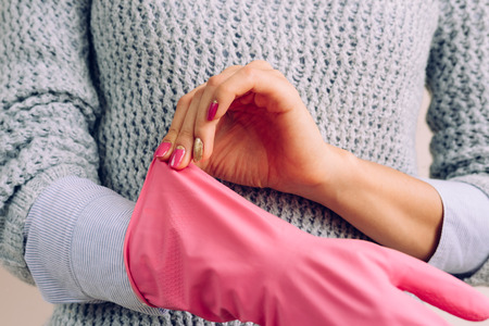 white shirt: Woman in a grey sweater and bright pink manicure wears rubber gloves for house cleaning