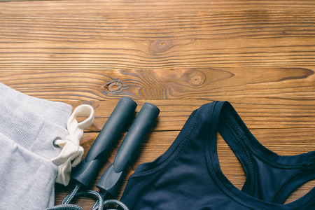 Sport Pants, a sports bra and jump rope. Womens sports clothing on a wooden background. Copy space.