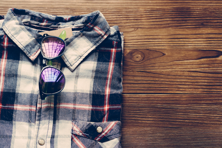 red shirt: Mens plaid shirt and colored glasses on a wooden background. Top view, copy space.