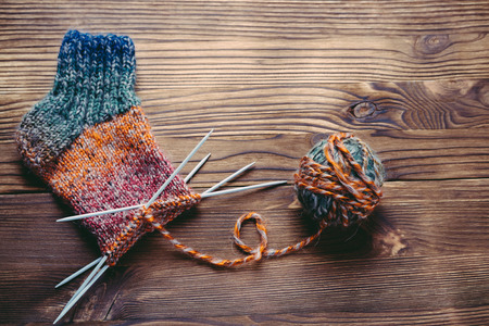 Knitted sock, ball of yarn and knitting needles on a wooden surface. Top view.