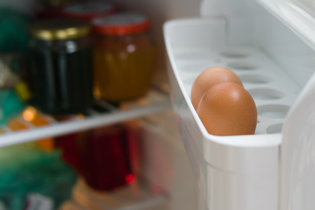 Two chicken eggs on a shelf of the refrigerator door close-up. Inside the refrigerator glass jars. Stok Fotoğraf