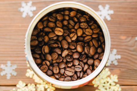 tin: Coffee beans in tin on a wooden table with decorations. Top view. Stock Photo