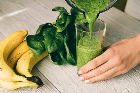 Female hand pours a smoothie of banana and spinach in glass on a wooden table Stock Photo