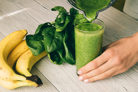 pouring: Female hand pours a smoothie of banana and spinach in glass on a wooden background