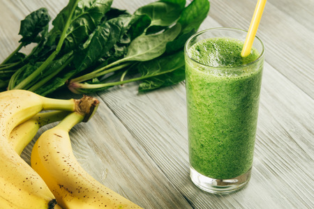 Green Smoothies of spinach and banana in a glass with yellow straw on white wooden background