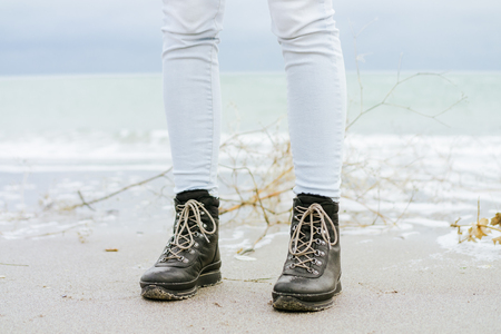 modern girl: Female feet in blue jeans and black winter boots standing in the sand against the sea