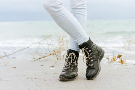 feet in sand: Female feet in blue jeans and black winter boots standing in the sand at the beach