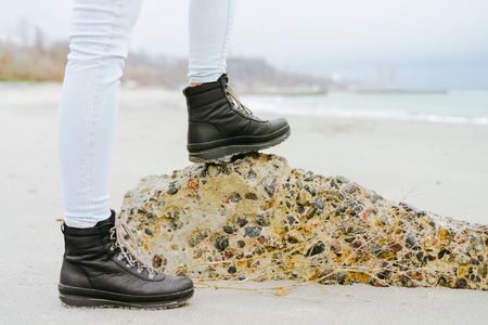 modern girl: Female feet in jeans and winter boots standing on a stone on the coast. Stock Photo