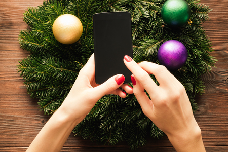 christmas manicure: Female hands with red manicure holding a mobile phone with a touch screen on the background of Christmas decorations Stock Photo