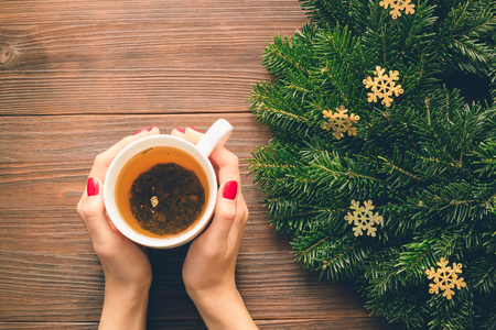 female christmas: Female hands with red manicure holding a cup of tea on a background of Christmas decorations. View from above. Stock Photo