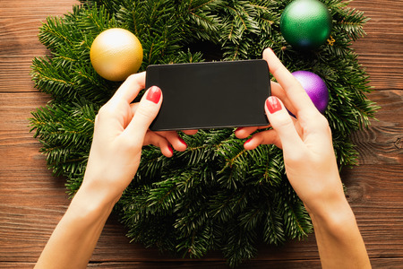 christmas manicure: Womens hands with red manicure holding a mobile phone with a touch screen on the background of Christmas decorations