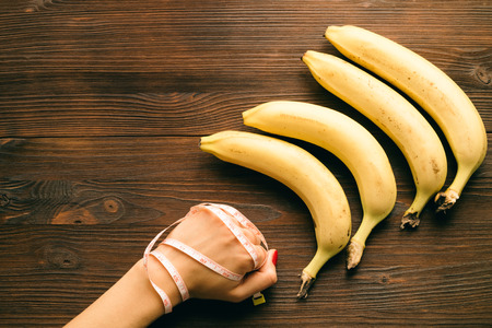 eating up: Female fist wrapped in measuring tape, lie near the bananas on a wooden table. Top view, concept. Stock Photo