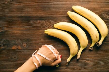 comiendo platano: Mujeres puño envuelto en cinta de medición, se encuentran cerca de los plátanos en una mesa de madera. Vista superior, el concepto.