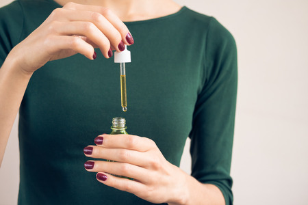 Female hands with a dark red manicure holding cosmetic oil in a bottle with pipette