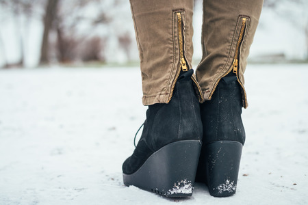 clasp feet: Female shoes on a platform in the snow, rear view