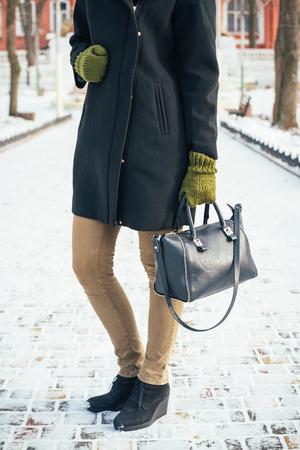 pies bonitos: Mujer delgada joven en un abrigo negro y guantes verdes que sostiene un bolso de mano y de pie en la acera de nieve