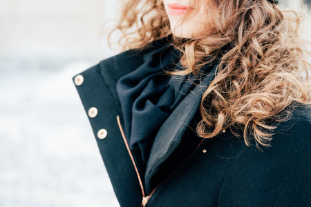 Details of womens clothing: girl with curly hair in black coat closeup outdoors Stock Photo