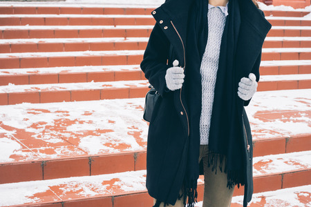 Young slim woman in unbuttoned black coat, a gray sweater and gloves walking along the snowy red ladder