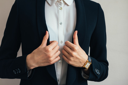 suit jacket: Woman wears a business suit jacket. In her hand wristwatch. Close-up of a woman in a business suit and wristwatch. Stock Photo