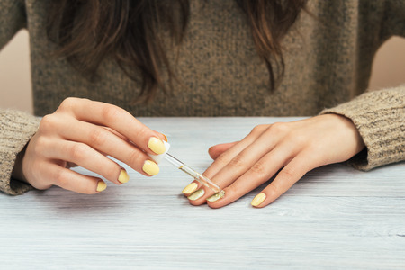 Woman in a brown sweater with yellow manicure applying cosmetic oil on the skin.
