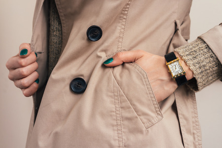 Woman put her hand in coat pocket, close-up