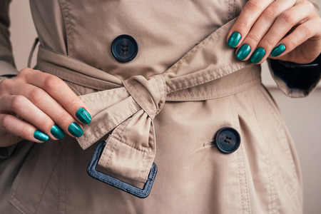 Female hands with a bright manicure tie belt on a coat, close-up